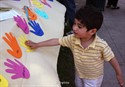 22May2011  Hassan Alsaedy, 2-1/2 of Kalamazoo tries out some handprints on the Skyridge Church of the Brethren display during Peace Pizzazz in Bronson Park Sunday afternoon.  The event was sponsored by the 6th Congressional Campaign for a Department of Peace and Skyridge Church of the Brethren.   (Special to the Gazette / John A. Lacko)