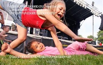 Myeisha Jackson, 5, of South Haven watches from the ground as sister Michaela, 7, tries a handstand at South Havens Harbortfest Friday evening in the Riverfront Park.