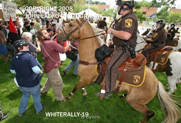 Kalamazoo Sheriff's deputies on horseback control protesters after a minor disturbance before the white supremacists rally Saturday afternoon in the parking lot of the Kalamazoo Department of Public Safety.