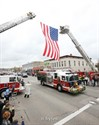 26April2011 The Kalamazoo Public Safety fire truck carrying the casket of slain KPSO Eric Zapata passes under a giant U. S. Flag held aloft by two KPS aerial fire trucks along West Michigan Avenue Tuesday afternoon. . ( Special to the Gazette / John A. Lacko)